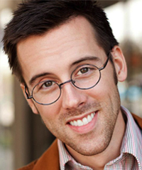 A man with glasses smiles at the camera.