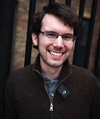 A man with glasses is smiling at the camera