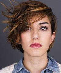 A woman with short hair looks at the camera.
