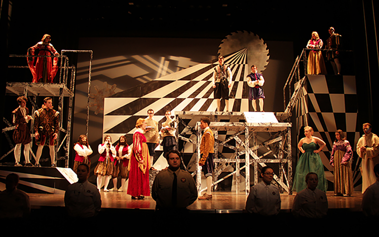 cast of actors on black and white checkered stage