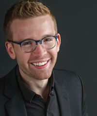 A young man with glasses and a suit smiles at the camera.