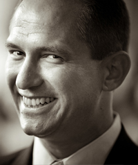 A black and white photo of a man in a suit smiling at the camera.