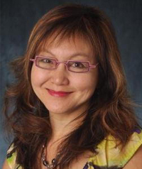 A woman with glasses smiles at the camera.