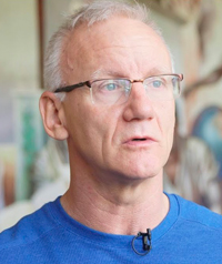 An older man with glasses looks away from the camera.