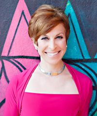 A woman with short red hair and a bright pink dress smiles at the camera.
