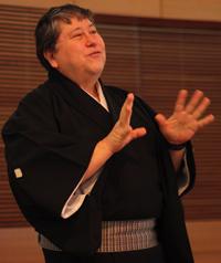 A man in a kimono is seen speaking publicly
