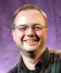 A man with glasses smiles at the camera