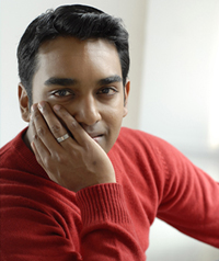A young man rests his face on his hand and looks at the camera.
