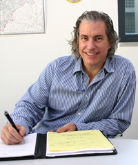A man write on a pad of paper while smiling at the camera