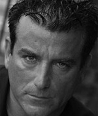 A black and white photo of a middle aged man looking sternly at the camera