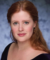 A woman with red hair and light eyes smiles at the camera.