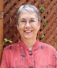 An older woman in a red button up shirt smiles at the camera.