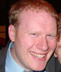 A man with red hair smiles at the camera.