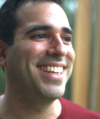 A man with a red shirt laughs while looking away from the camera