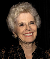 An older woman with white hair smiles at the camera.