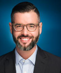 A man with glasses and a beard smiles at the camera.