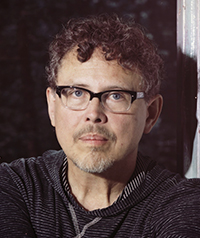 A man with glasses looking at the camera