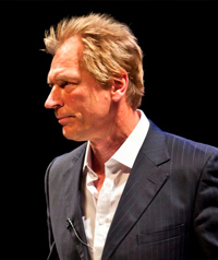A man in a suit looks away from the camera.