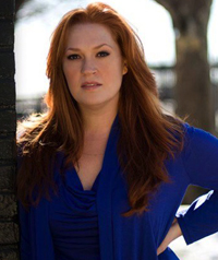 A woman wearing a blue shirt looks at the camera.