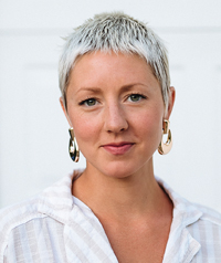 woman with silver hair and large earrings