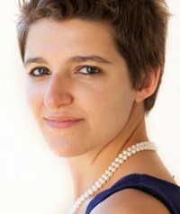woman with short brown hair and pearl necklace