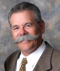 An older man with a large twirled mustache and suit smiles at the camera.