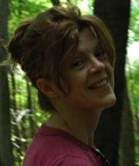 woman with brown hair up in the woods