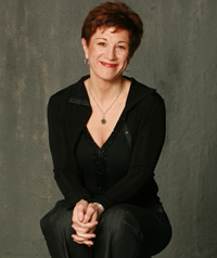 A middle aged woman with short red hair smiles at the camera.