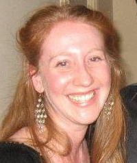 A woman with red hair smiles at the camera