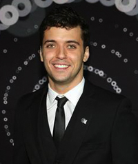 A man in a suit smiles at camera.
