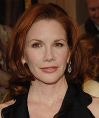 A woman with red hair smiles at the camera.
