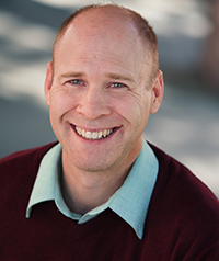 A middle aged man in a red sweater smiles at the camera.