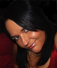 A woman with dark hair covering one eye smiles up at the camera.
