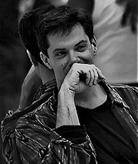 A black and white photo of a man covering his face while smiling.