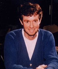 A man in a blue sweater smiles at the camera.