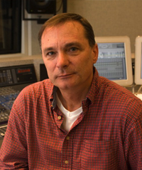 An older man in a red button up shirt looks at the camera.