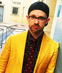 A man in a yellow blazer and glasses looks at the camera.