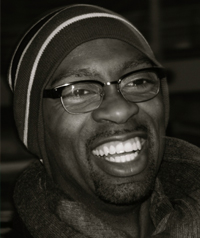 A man in glasses laughs at the camera.