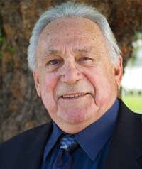 An older man in a suit smiles at the camera.