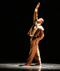 A man is shown in a spotlight on a stage.