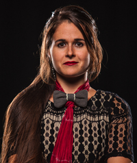 A woman with a bow tie looks at the camera