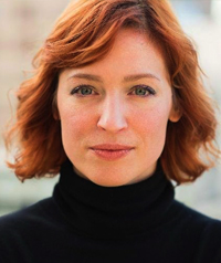 A woman in a black turtleneck smiles at the camera