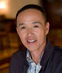 A middle aged man with black hair smiles at the camera.