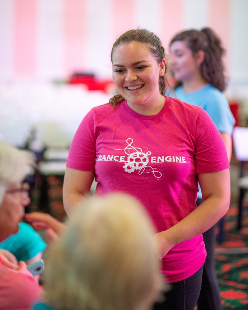 woman wearing a pink t-shirt talk to to people sitting down