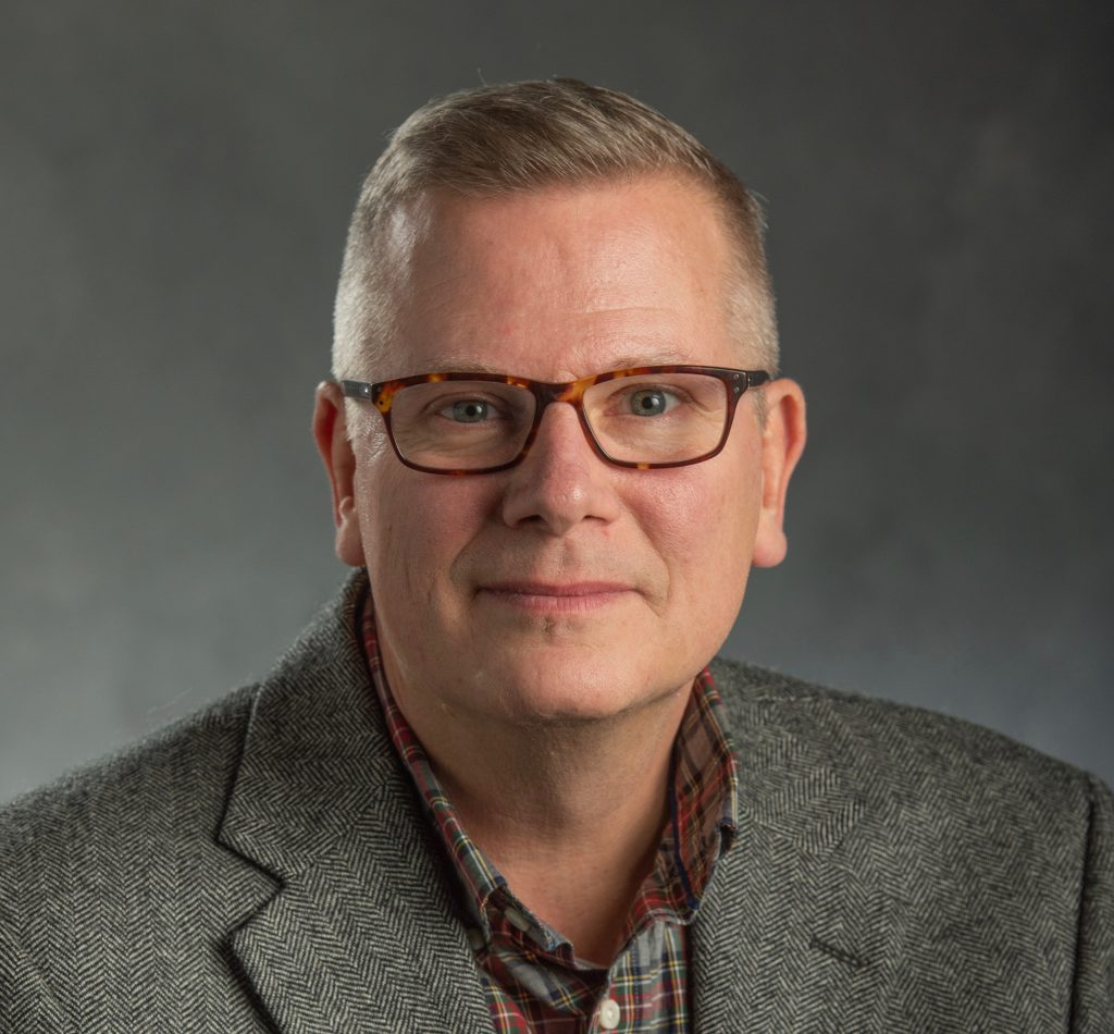 man wearing glasses and a gray jacket