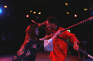 two actors in a close duel with swords, glaring at one another