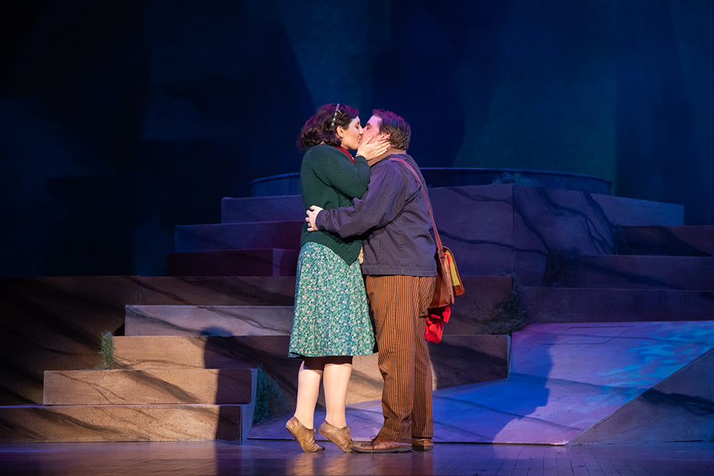 A woman and man kiss on a darkly lit stage