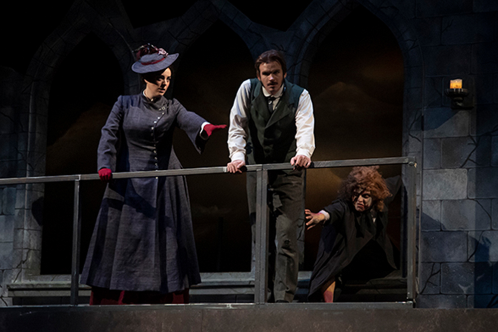 A woman dressed in 1800s attire reaches for a man leaning on a balcony while another person crawling, also reaches for the man