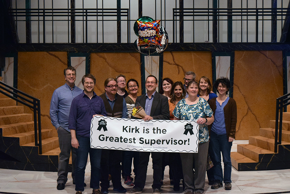 """A group of people stand on a stage holding balloons and a sign that reads """"Kirk is the Greatest Supervisor"""""""