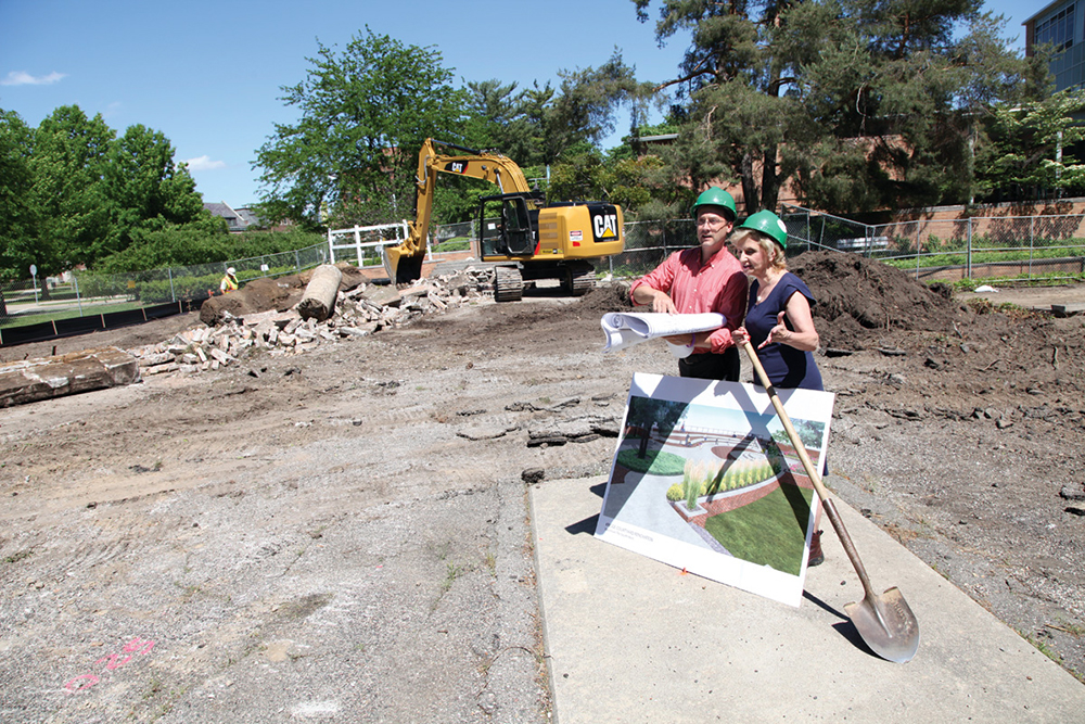 A man and woman stand in a construction zone wearing green helmets, with a shovel and design plans. A yellow excavator digs in the background.